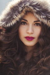 Young beautiful woman with black curly hair and red lipstick walking in the city park