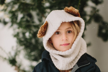 a girl wearing a winter hat with ears looks at the camera standing outside