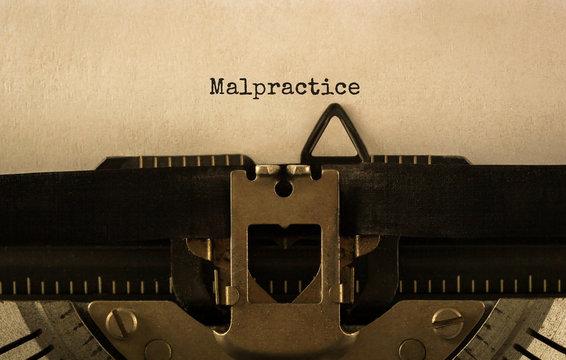 Text Malpractice typed on retro typewriter