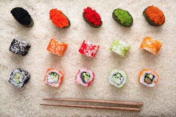 Top view on sushi rolls and gunkan near chopsticks on white rice background and texture, flat lay