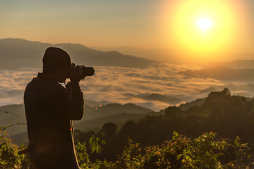 Photograph takes photos of daybreak above heavy misty valley. Landscape view of misty autumn mountain hills and hiker silhouette