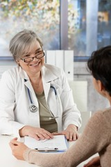 Mature female doctor talking to patient