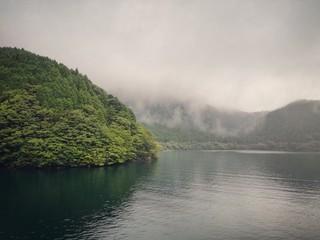 Paisaje de lago y montañas en tarde de verano con nubes