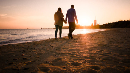 Couple walking on the beach in autumn