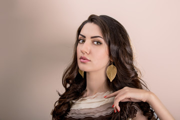 Portrait Of Beautiful Young Mediterranean And Middle Eastern Brunette Hair Girl With Leaf Shape Gold Earrings, Glossy Lips Make Up And Red Nails. Studio Shot On Beige Background