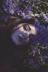 Beautiful young woman amongs the lilac flowers