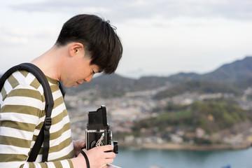 クラシックカメラで風景を撮影する男性