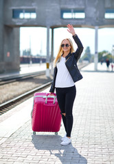 A girl with a pink suitcase is standing at the railway station