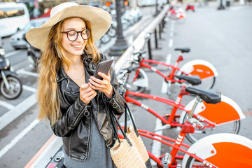 Young woman tourist renting a city bicycle with smartphone in Barcelona
