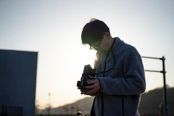 クラシックカメラで写真を撮影する男性