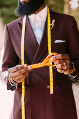 Close up of a tailor in a suit holding scissors