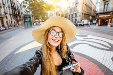 Young woman tourist making selfie photo standing on the central street with famous colorful tiles in Barcelona city