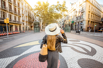 Young woman tourist walking back on the central street with famous colorful tiles in Barcelona city
