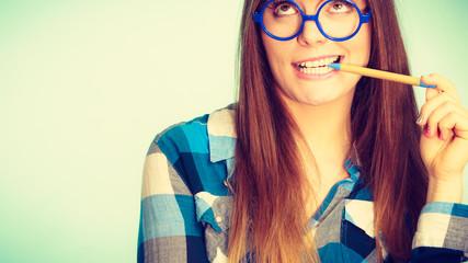 Happy nerdy woman in glasses holding pen