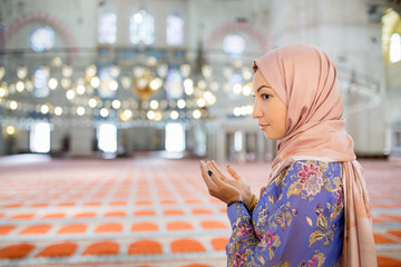 A woman in a scarf praying in a mosque, Turkey