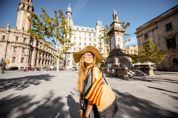 Young woman tourist walking with catalan flag on the Antonio Lopez square in Barcelona city