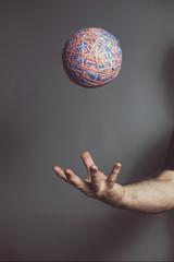 Hand throwing elastic band ball...