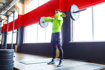 A young bearded man is training with a barbell in the gym.