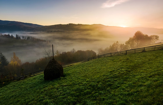 haystack and wooden fence on hillside at foggy autumn morning in mountains. beautiful rural scenery