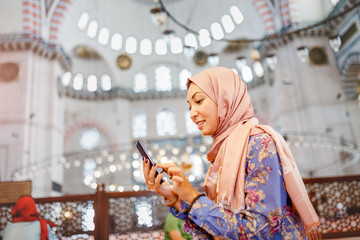Young muslim woman with phone in mosque