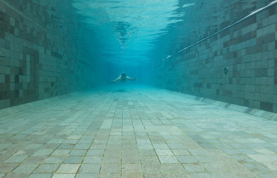Man diving underwater of a swimming pool