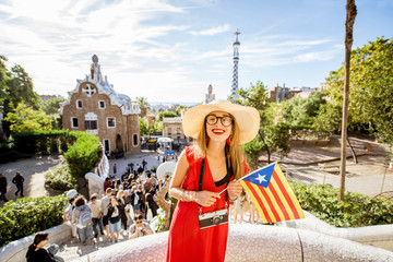 Woman tourist in red dress enjoying great view standing with catalan flag on the terrace in famous Guell park in Barcelona