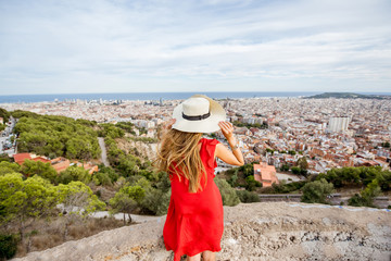 Young woman tourist in hat enjoying great cityscape view on Barcelona