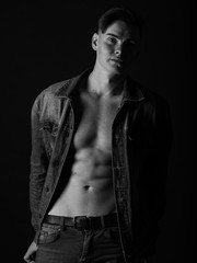 Gorgeous fit man in a jeans jacket, shirtless on a black background. Black and white sexy man concept.