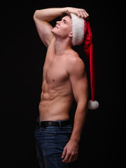 Shirtless Santa in a red hat on a black background. Handsome Christmas guy. New Year party concept.