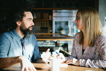 Man and woman having a conversation over coffee in a cafe