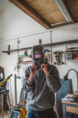 Man wearing welding mask at the workshop