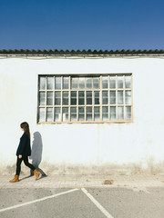 Beautiful young woman walking in front a old factory wall.