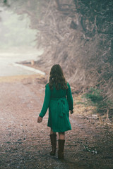 girl in the woods walking down a driveway