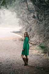 girl in green dress walking up a driveway in the woods