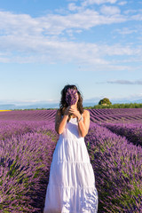 Woman hiding behing lavender flowers in a field