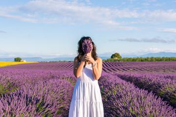 Woman hiding behing lavender flowers in a field
