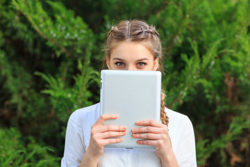 A young girl in the park covered her face with a tablet.