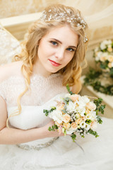 Beautiful young Bride with blonde hairs in a bedroom. Classic white wedding dress. Half-length portrait