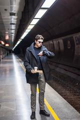 Modern man waiting train on platform.
