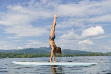 Young Girl doing Yoga on Stand up Paddle Board