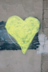 Yellow heart shape painted on wall of building