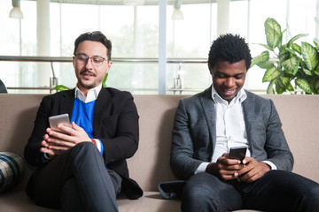 Two multicultural men sit on sofa, smile and hold mobile phones. Internet social media addiction concept.