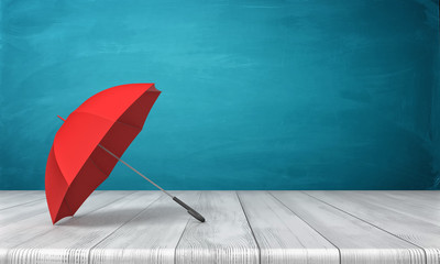 3d rendering of a single red open umbrella lying on its side with an open canopy on a wooden surface on blue background.