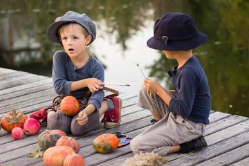 Little children paint small Halloween pumpkins