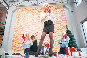 Drunk people having fun in Santa hats on a festive background. New year office party concept. Copy space.