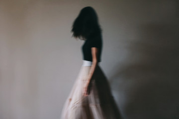 Old fashioned, moody looking, image of woman moving in a long, full, skirt