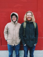 Two good smiling friends in warm jackets standing in front of a red wall