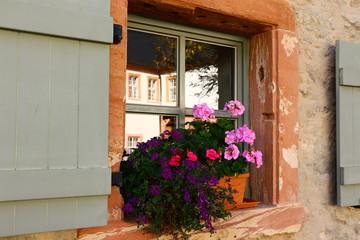 Blumenschmuck vor einem Sprossenfenster