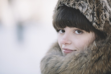 winter close-up of the young woman with fur hat
