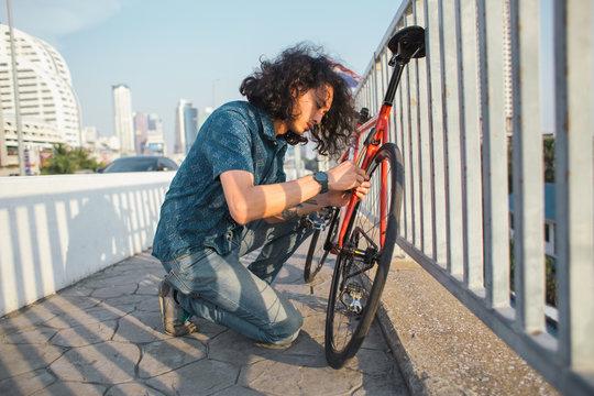 Asian man fixing his bicycle
